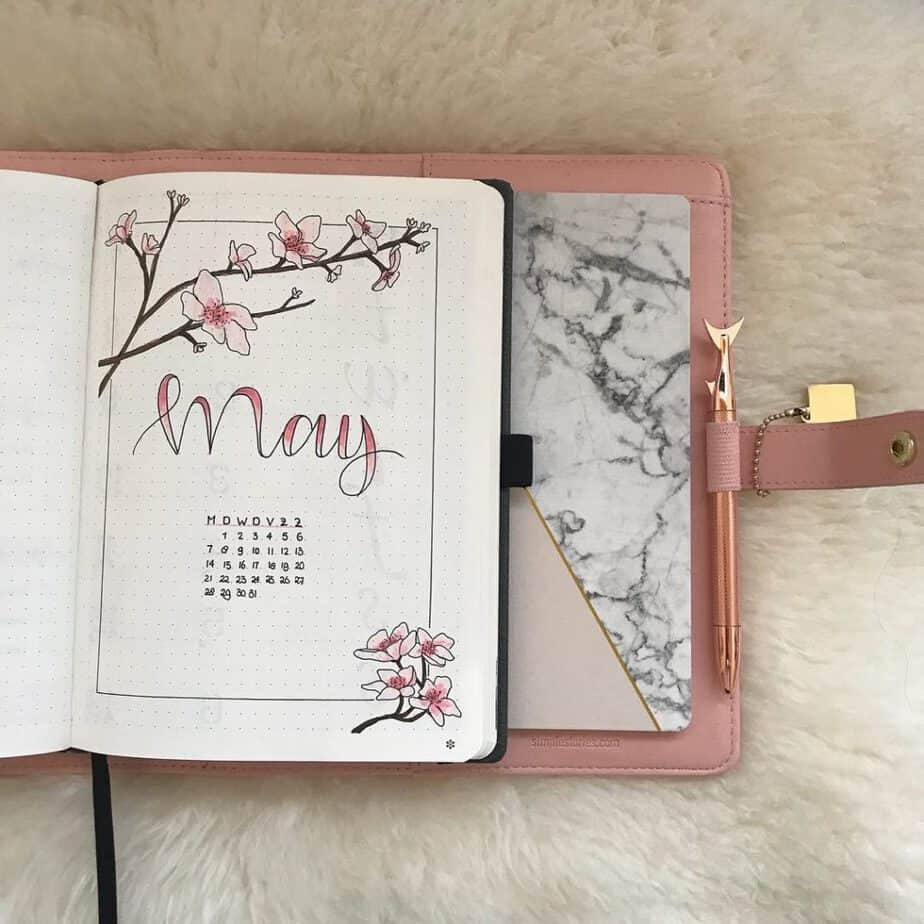 Delicate May cover page from @butterfliesandletters What don't you love about this beautiful May bullet journal cover page? It's filled with gorgeous ombre in the lettering and flowers. The doodles are light and pretty. The frame around the page is a nice touch as well.