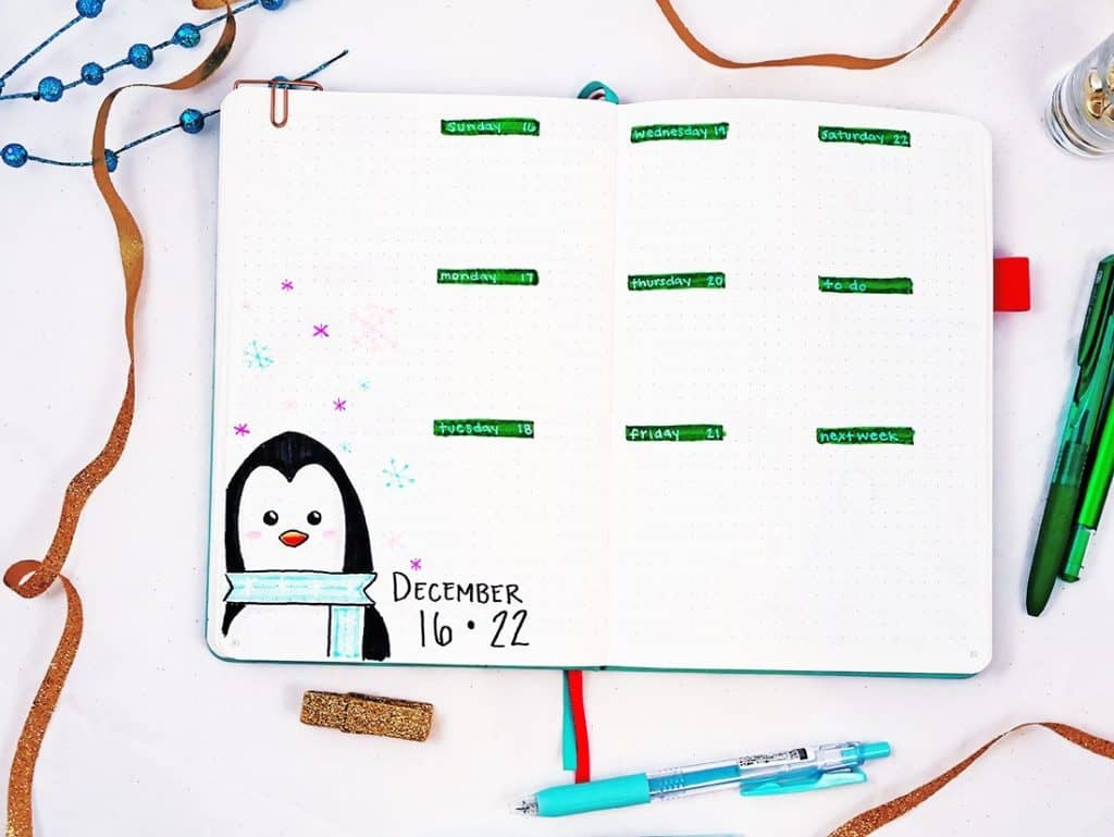 Bullet journal holiday theme weekly layout for December with penguin and snowflake doodles