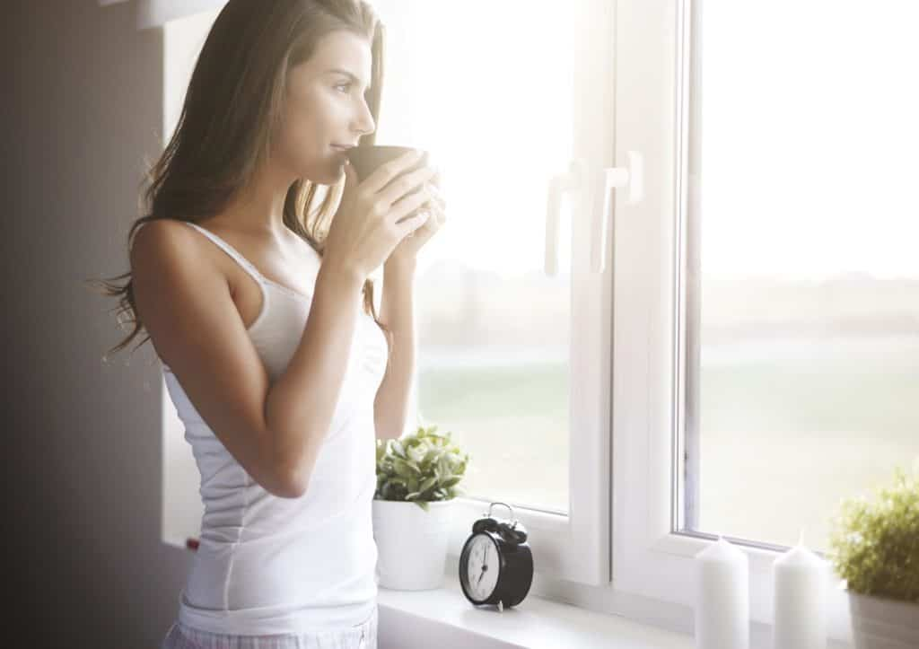 Woman soaking in the sunshine and drinking coffee as part of her daily morning routine.